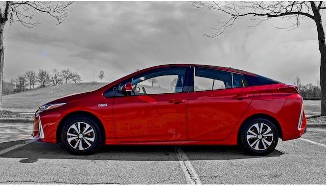 Вид сбоку на красный Toyota Prius Prime